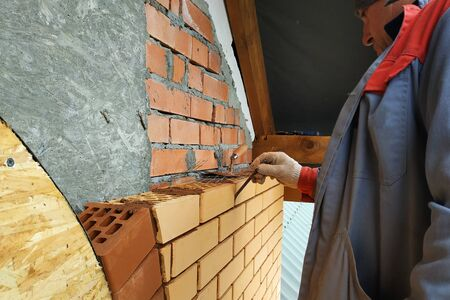 The master in a blue overalls builds a wall of face brick.2020