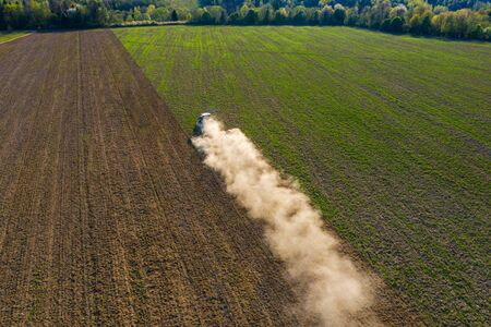 A crawler tractor cultivates the soil in an agricultural field. Top view flying on a drone. Tracking in a circle.