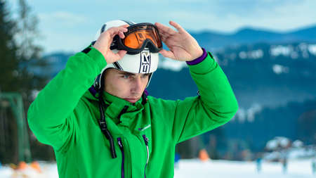 A man skier wearing a helmet briko and ski goggles swans before training for safety. A professional snowboarder prepares for competitions 2021. Yablunytsya, Ukraine : February 5, 2019 写真素材 - 147998033