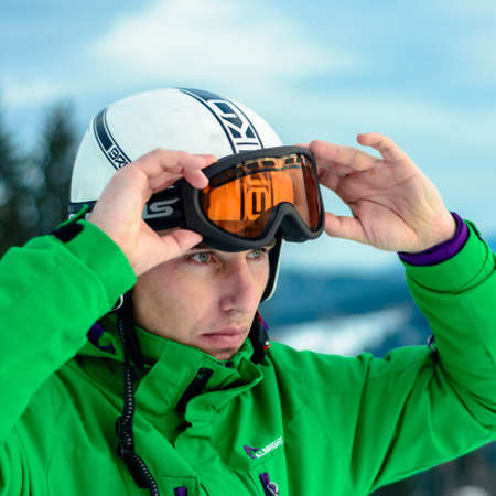 A man skier wearing a helmet briko and ski goggles swans before training for safety. A professional snowboarder prepares for competitions 2021. Yablunytsya, Ukraine : February 5, 2019 写真素材 - 147998037