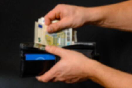 Man hand pulling money from wallet, black background and black wallet. Blurred and defocused image. Zdjęcie Seryjne