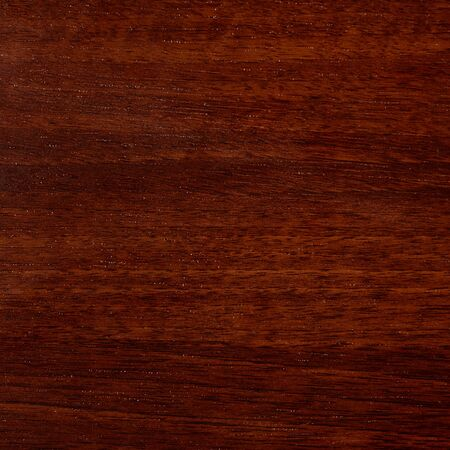 Varnished red tree with original texture. Beautiful brown wood background on lacquered textured plywood. Dark wood table texture background top view.