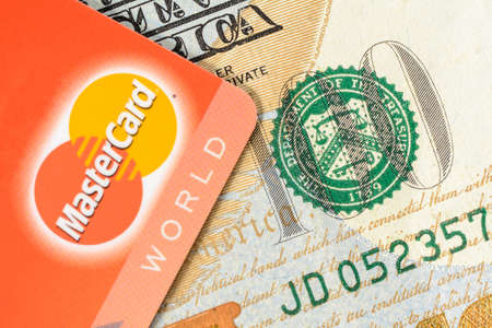 Lviv, Ukraine - 26 April 2019 : A red card with a MasterCard logo is placed on a one hundred dollar banner close-up 2020 Publikacyjne