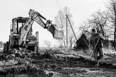 Trostyanets, Ukraine December 20, 2019: An excavator in the village paves the way, digs soil and transfers concrete slabs.2020 Publikacyjne