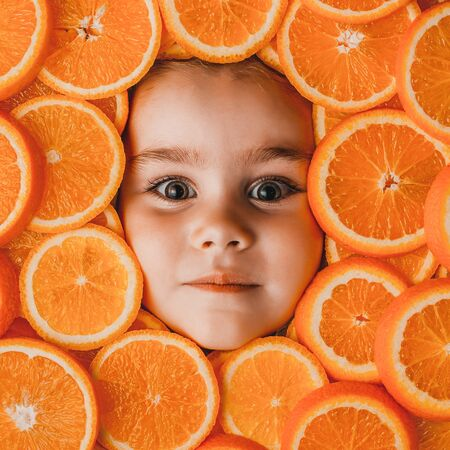 Face of a little beautiful girl close up on a background of sliced orange. The concept of a healthy lifestyle for children in a pattern of fruits. Zdjęcie Seryjne
