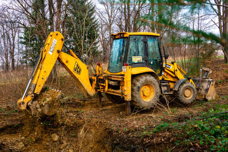 Trostyanets, Ukraine December 20, 2019: excavator digs soil in pond forest.2020 Publikacyjne