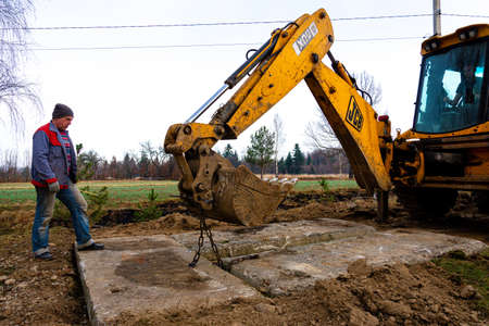 Trostyanets, Ukraine December 20, 2019: an excavator in the village paves the road in a private yard.2020