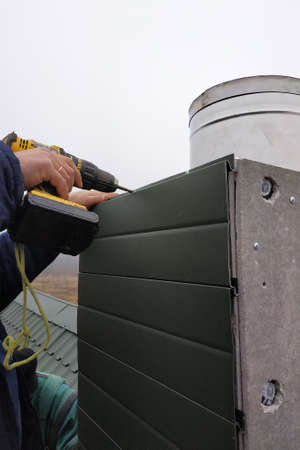 Facing a new chimney on a new two-story house, the worker uses a drill battery, does not enjoy protection, dressed in winter overalls 2020.