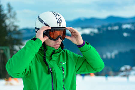 A man skier wearing a helmet briko and ski goggles swans before training for safety. A professional snowboarder prepares for competitions 2021. Yablunytsya, Ukraine: February 5, 2019