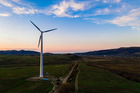 Wind turbine, alternative energy, wind energy, one windmill in a field in the mountains, top view of a wind turbine at sunset. 2021