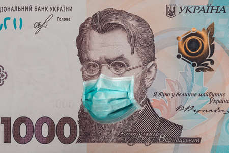 Banknote of 1000 hryvnia depicting Vladimir Vernadsky in a medical mask during the economic crisis and pandemic of the coronavirus in Ukraine. Qualitative montage closeup.