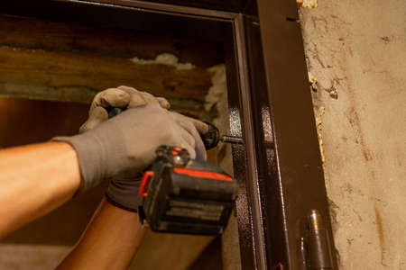 The master drills holes with a hand drill in a metal door box, close-up, installation of new doors. 2020