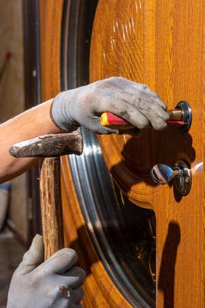The master worker installs a door lock in the front door, metal doors with a polymer coating. 2020 写真素材