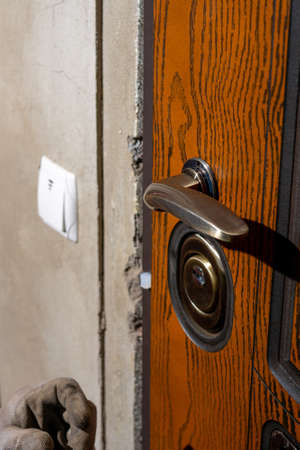 The young master skillfully and professionally installs a lock in the front door of a private house, a close-up of twisting. 2020