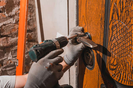 Close-up, the carpenter installs a custom lock in the front metal door, using a drill and hammer and other tools. 2020