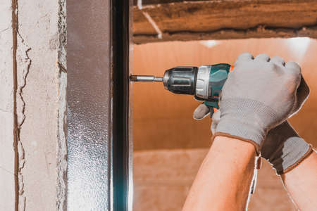 The carpenter drills holes in the wall and the metal door frame with a drill, later screws the screws and fastens the door frame to the wall. 2020