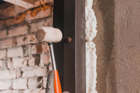 The carpenter, after foaming and insulating the front door, knocks with a hammer for good adhesion of the foam to the wall and door. 2020