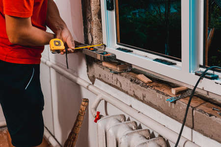 The man performs installation work with the window, for this he also uses a tape measure, measures distances and fastens the window to the wall.
