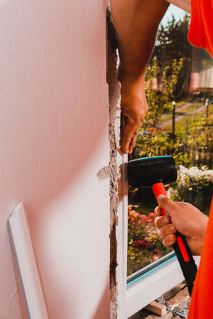 the man assembles the window, installs the double-glazed windows and fastens the corner posts with a rubber hammer to hold the glass.