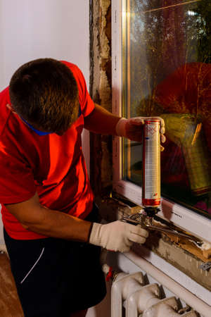 Using polyurethane foam to fill the gaps during the installation of the window, Close view, details of the replacement process, the worker uses a foam gun.