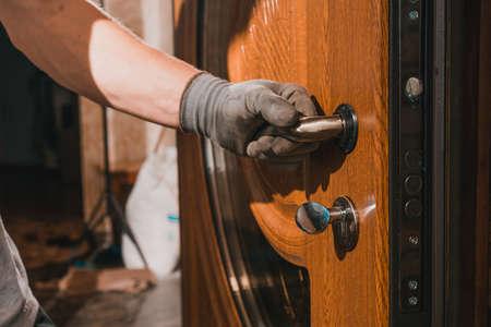 The master worker installs a door lock in the front door, metal doors with a polymer coating.