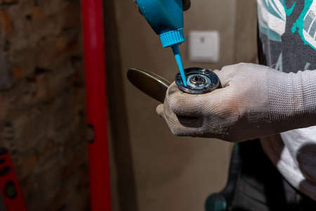 The young master skillfully and professionally installs a lock in the front door of a private house, a close-up of twisting.
