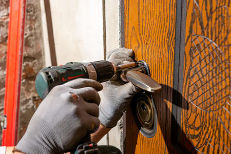 Close-up, the carpenter installs a custom lock in the front metal door, using a drill and hammer and other tools. 免版税图像