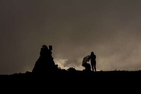 Couple of tourists in the clouds on top of Mount Brebeneskul, tourists standing on top in the raincoats, gloomy weather. 2020