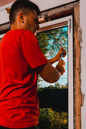 The master fixes a window to a wall by means of a manual key, installation of a new window, a plastic window, process of work close-up. 2020