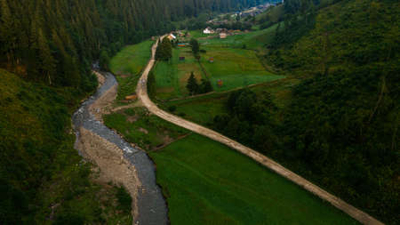 Carpathian river Bila Tisa, the largest tributary of the Danube, Ukrainian mountain river, top view of the river and the road In the village of Luhy. 2020