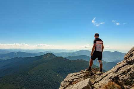 A tourist on top of a large stone block, the top of Smotrych mountain, one of the rocky peaks of the Ukrainian Carpathians. 2020 免版税图像