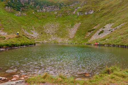 Alpine lake Brebeneskul, the cradle of the Carpathians, a couple of tourists near the lake, reflection in the water. 2020 免版税图像