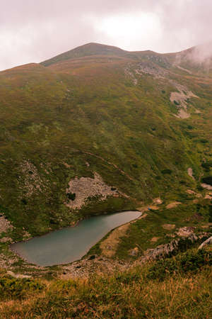 Lake Brebeneskul in the clouds, a view of the lake from the Montenegrin ridge, high-altitude ecologically clean lake in the Carpathians, a nature reserve. 2020 免版税图像