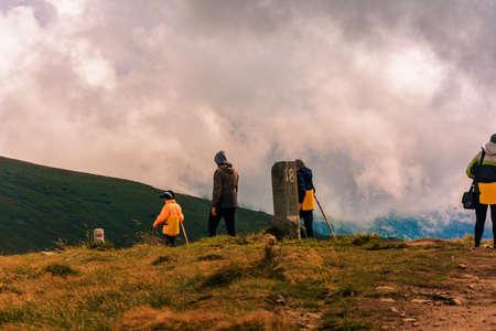 Tourists follow a mountain trail on a tourist sign to the next destination. 2020
