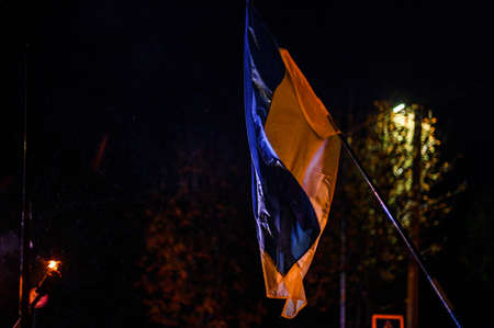 Ukrainian flag during a protest rally on Independence Square at night 2021