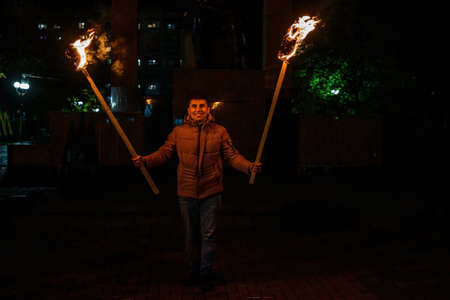 The man is holding two torches, a peaceful participant of the action, an evening with torches. 2020