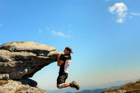 Tourist climber makes a climb on a large rocky rock without protection, the Ukrainian Carpathians, danger and extreme. 2020
