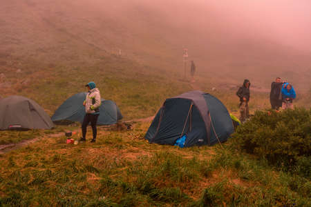 Tourists and tents near the lake, fog in the mountains near the lake, rain clouds in the Carpathians, a tent camp near the lake, Lake Brebeneskul. 2020