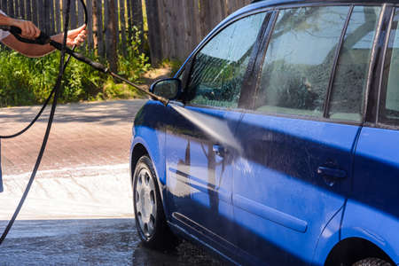 Car wash, rinse with excess water and foam on the car, clean on a wet car. 2020