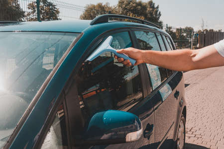 The man takes the remnants of water from the glass after washing the car at the self-service car wash, the car is blue. Archivio Fotografico