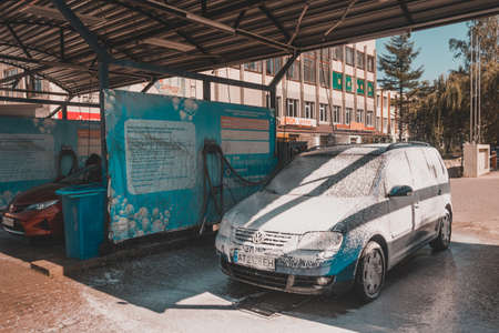 Ivano-Frankivsk, Ukraine August 14, 2020: car wash at a self-service car wash, a man washes his car. 2020 新聞圖片