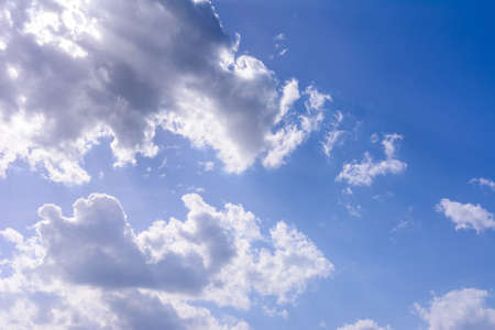 Blue sky and white cumulus clouds, clouds obscure the sun, sunlight can be seen from behind the clouds. 2020