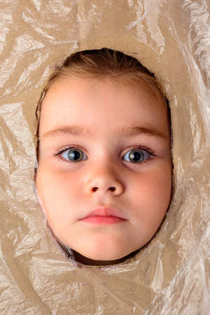 A little girl holds her head in a cut hole in cardboard, cardboard is a decoration for a photo. 2020