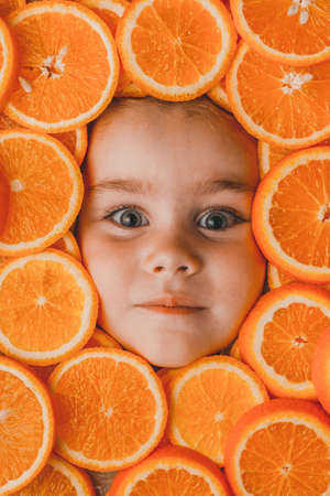 The face of a beautiful little girl is surrounded by pieces of sliced orange, orange useful fruit rich in vitamin C 2021. 版權商用圖片