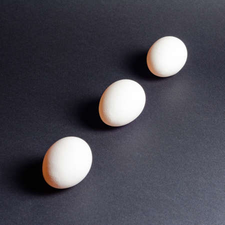 Three white eggs on a black background, dietary and healthy food rich in protein 2021