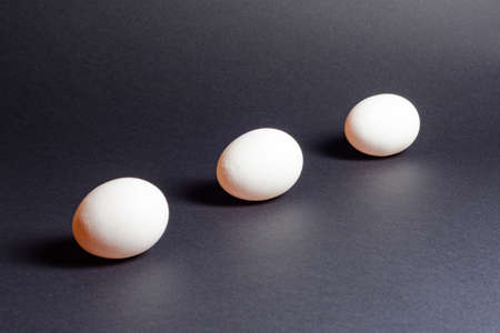 Eggs on a black background, three eggs in a row, shadow on the background of eggs, healthy and diet food. 2020