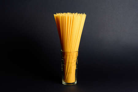 Spaghetti in a glass on a black background, Italian cuisine and cooking. 2020