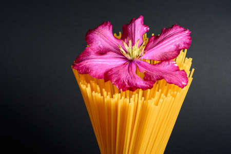 Spaghetti - yellow pasta, Italian dishes and cuisine, spaghetti in a glass and a decorative flower. 2020