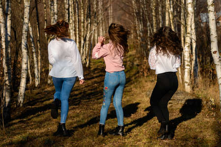 Young group of girls walking in autumn park, autumn clothes and autumn walk. 2020