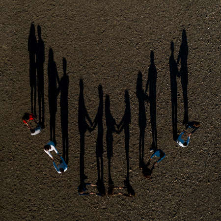 A group of children stand on the road, resulting in shadows, top view. 2020